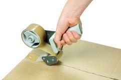 Sealing box. Sealing cardboard box with adhesive packing tape royalty free stock photography
