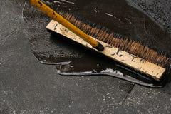 Sealing a damaged asphalt drive way. Sealing a damaged asphalt blcktop drive way with large brush stock images