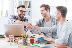 Sealing a deal. Business people shaking hands while sitting at the desk in office Royalty Free Stock Images
