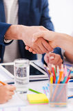 Sealing a deal. Close-up of business people in smart casual wear shaking hands while sitting at the table together Royalty Free Stock Photography