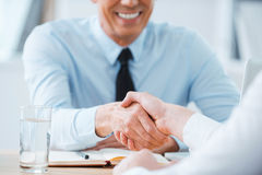 Sealing a deal. Close-up of two business people shaking hands while sitting at the working place Royalty Free Stock Photo