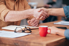 Sealing a deal. Close-up of two men shaking hands while sitting at the wooden desk Stock Photos