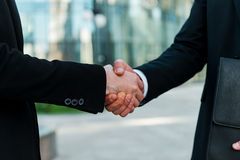 Sealing a deal. Close-up of two young businessmen shaking hands while standing outdoors Stock Photography