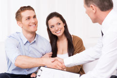 Sealing a deal. Happy young men shaking hand to financial agent while sitting together with his wife Stock Photo