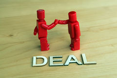 Sealing the deal. One figure shaking hands with the other figure Royalty Free Stock Images