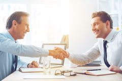 Sealing a deal. Side view of two business people shaking hands while sitting at the table in office Royalty Free Stock Photos