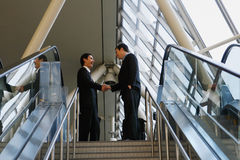 Sealing the Deal at the top of the stairs. Two businessmen shaking hands at the top of a stairway Royalty Free Stock Photography