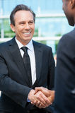 Sealing a deal. Two business men shaking hands and smiling while standing outdoors Royalty Free Stock Image
