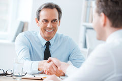 Sealing a deal. Two business people shaking hands while sitting at the working place Royalty Free Stock Images