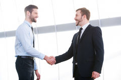 Sealing a deal. Two cheerful business men shaking hands and smiling while standing indoors Stock Photography
