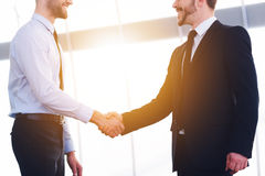 Sealing good deal. Two cheerful business men shaking hands and smiling while standing indoors Stock Images