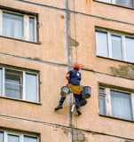 Sealing of seams between plates. The work of steeplejack repair block of the house Royalty Free Stock Photography