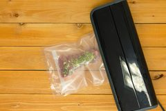 Sealing a vacuum packed flat iron steak. In clear plastic for freezing or sous-vide cooking on a heated appliance viewed from above on a wooden table royalty free stock image