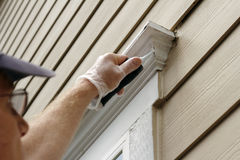 Sealing Window Leaks. Man outdoors filling holes that developed around an exterior home window frame Stock Photos