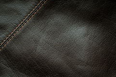 Seam on the black leather. Seam on the brown leather (vertical orientation royalty free stock photo
