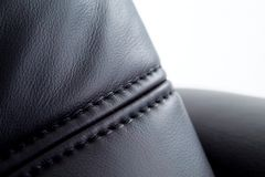 Seam on black leather. Furniture with white background. Shallow depth of field stock photos