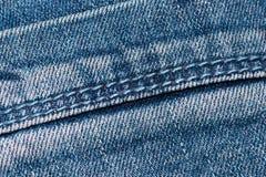 Seam on blue denim fabric. Texture of blue denim fabric with a seam. Close-up Stock Photography