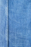 Seam on blue jeans background. Royalty Free Stock Image