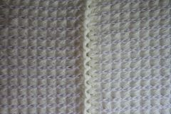 Seam between two parts of white knitted fabric. Seam between two parts of ivory knitted fabric Stock Photo