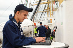 Seaman of russian ship Kruzenshtern works. STAVANGER - JULY 28: Seaman of russian ship Kruzenshtern works with laptop at Stavanger Tall Races on July 28, 2011 in Royalty Free Stock Image