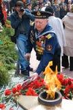 Seaman veteran. ULAN-UDE, RUSSIA - MAY 9: An elder seaman veteran lays flowers to eternal flame on annual Victory Day, May, 9, 2009 in Ulan-Ude, Buryatia, Russia Stock Photo