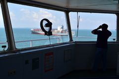 Seaman on the watch, looking at the container vessel passing royalty free stock photography