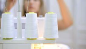 Seamer stelt de witte draad van de spoel in de naaimachine in werking stock footage