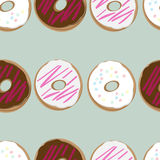 Seamless design of fresh doughnuts. Seamless background design of fresh doughnuts, or donuts, glazed with chocolate and pink and white icing covered in sprinkles Royalty Free Stock Image