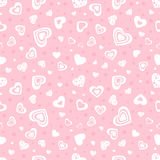 Seamless background with hearts and small circles. Pink seamless background with the image of the white hearts of different sizes and different decoration and Royalty Free Stock Photography