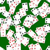 Seamless background playing cards randomly scattered on a green table Royalty Free Stock Photos