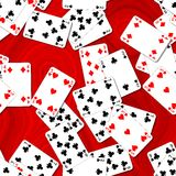 Seamless background playing cards randomly scattered on a red table Royalty Free Stock Photo