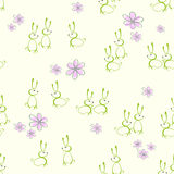 Seamless background with silhouettes of Easter bunnies. Seamless bright green background of Easter bunnies and flowers Royalty Free Stock Photography