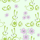 Seamless background with silhouettes of Easter bunnies. Seamless bright green background of Easter bunnies and flowers Royalty Free Stock Photos