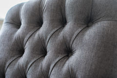 Seamless background texture close up of a grey sofa back with button detail on a thick cloth. Stock Photo