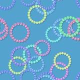 Seamless beaded bracelets pattern on blue Stock Photography