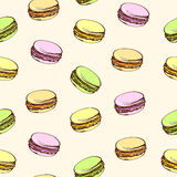 Seamless beige background with colored macaroons. Cartoon style. Royalty Free Stock Photo