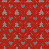 Seamless Christmas nordic knitting vector pattern with fir-trees, hearts and decorative line. On red background Stock Images