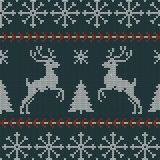 Seamless Christmas nordic knitting vector pattern with fir-trees, snowflakes, deer and decorative stripes. On dark green background Royalty Free Stock Images