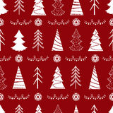 Seamless Christmas  pattern with fir-trees, snowflakes, garlands. On a red background Stock Images