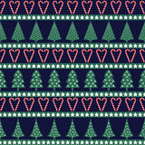 Seamless Christmas pattern - varied Xmas trees, stars and candy canes. Happy New Year and Merry Xmas background. Vector design for winter holidays on dark blue Stock Images