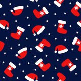 Seamless Christmas pattern with xmas socks, stars and Santa hats. Happy New Year and Merry Xmas background. Vector design for winter holidays. Winter holidays Stock Images
