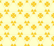 Seamless colored pattern. Print of dark yellow clovers four and three leaves and lines on light yellow background. Royalty Free Stock Images