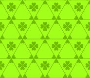 Seamless colored pattern. Print of green color clovers four and three leaves and lines of triangles on light green background. Seamless colored pattern. Print Royalty Free Stock Photo