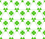 Seamless colored pattern. Print of green color clovers four and three leaves and lines of triangles on white background. Seamless colored pattern. Print of Royalty Free Stock Photography