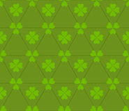 Seamless colored pattern. Print of light green clovers four and three leaves and lines of triangles on green color background. Royalty Free Stock Photography