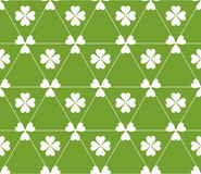 Seamless colored pattern. Print of white clovers four and three leaves and lines of triangles on green color background. Stock Image