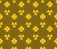 Seamless colored pattern. Print of yellow clovers four and three leaves and lines of triangles on brown color background. Seamless colored pattern. Print of Stock Images