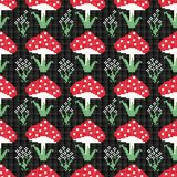 Seamless  pattern with red mushrooms and flowers on a black background. Stock Images