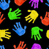 Seamless dark background with colored handprints. Seamless dark background with bright colored handprints Royalty Free Stock Image