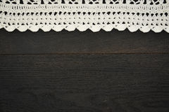 Seamless dark wooden background with lace horizontal. Old grunge dark wooden background texture with a stripe of white lace on top Royalty Free Stock Images